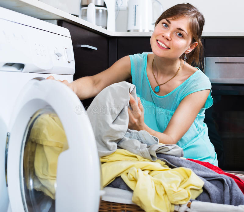 Woman enjoying clean clothes after laundry royalty free stock photos