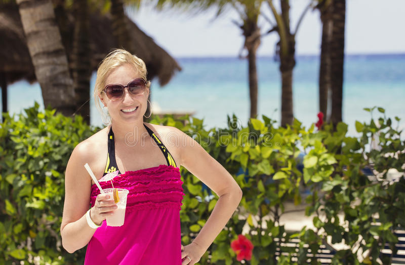 Woman enjoying a cocktail drink by the beach stock images