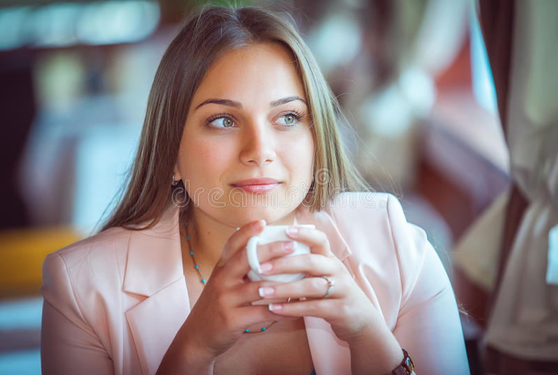 Woman Enjoying A Cup Of Coffee in Cafe. Young Attractive Woman Enjoying A Cup Of Coffee in Cafe stock photo
