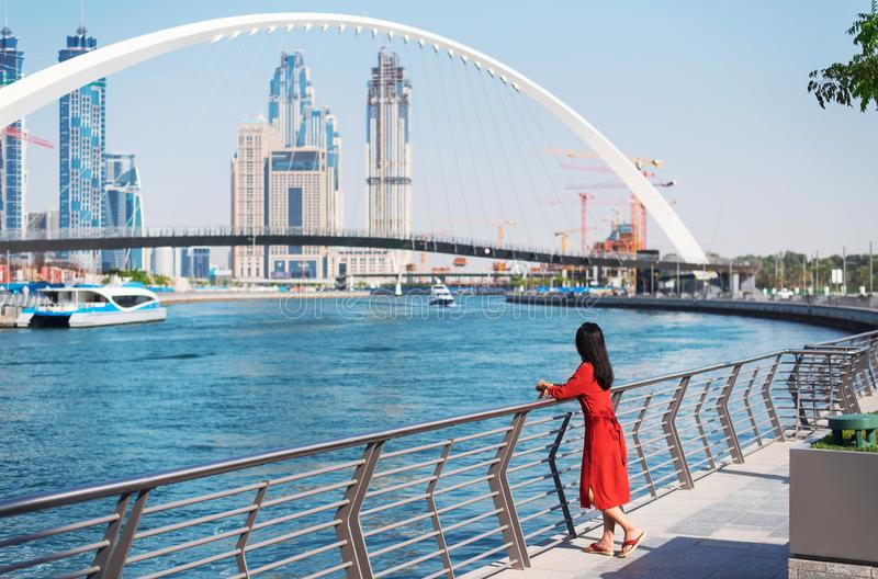 Woman enjoying Dubai view from the water canal. Woman enjoying view of Dubai from the water canal female girl skyline tolerance bridge expo tourist footbridge royalty free stock photography