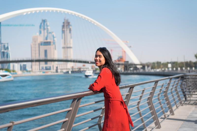 Woman enjoying Dubai view from the water canal. Woman enjoying view of Dubai from the water canal female girl skyline tolerance bridge asian chinese expo tourist royalty free stock image