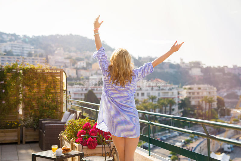 Woman enjoying early morning on balcony. With hands up high royalty free stock photos