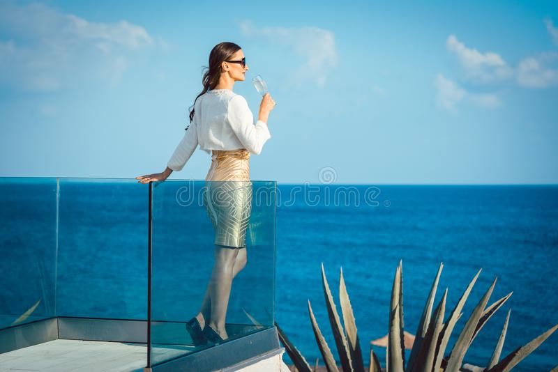 Woman enjoying glass of champagne at the sea royalty free stock photography