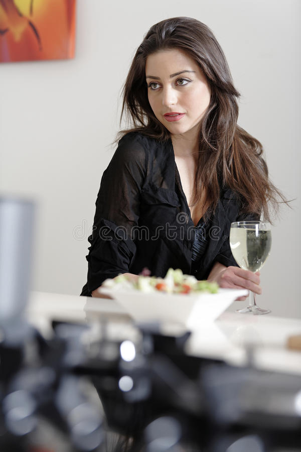 Woman enjoying a glass of wine. Beautiful young woman enjoying a glass of wine in her kitchen, while preparing food royalty free stock photography