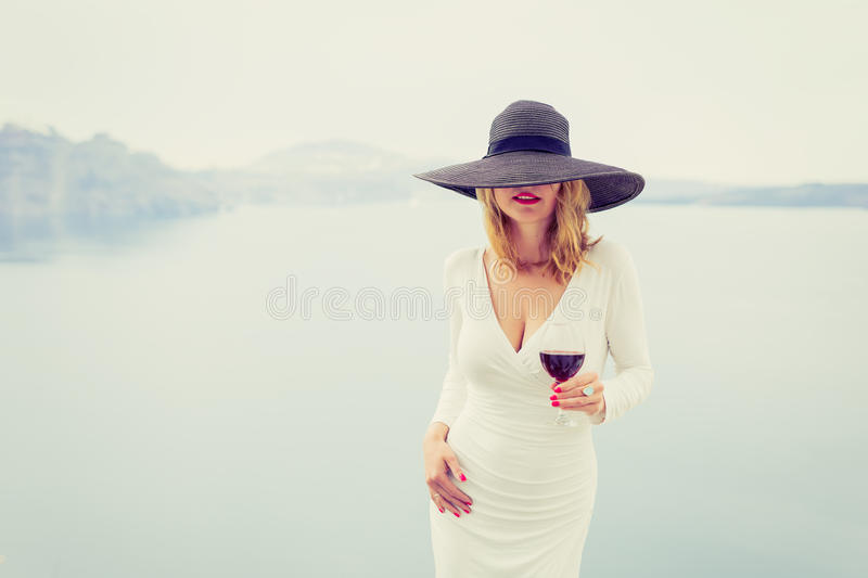 Woman enjoying glass of wine. Retro, vintage style filter. stock image