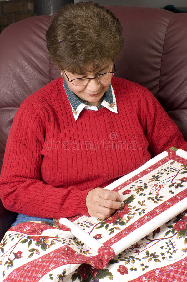 Woman enjoying hand quilting. A woman hand quilting a colorful red and green floral quilt panel stock image