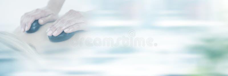 Woman enjoying hot stone massage at health spa royalty free stock image