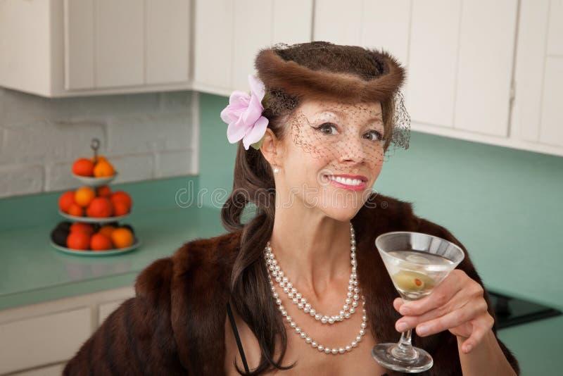 Woman Enjoying Martini. Caucasian woman wearing veil and mink coat enjoying martini in kitchen royalty free stock photo