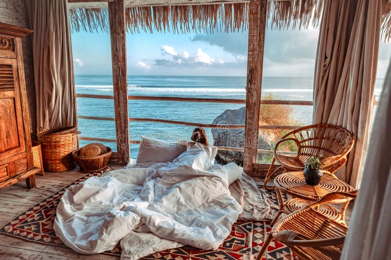 Woman enjoying morning vacations on tropical beach bungalow looking ocean view Relaxing holiday at Uluwatu Bali ,Indonesia stock photos