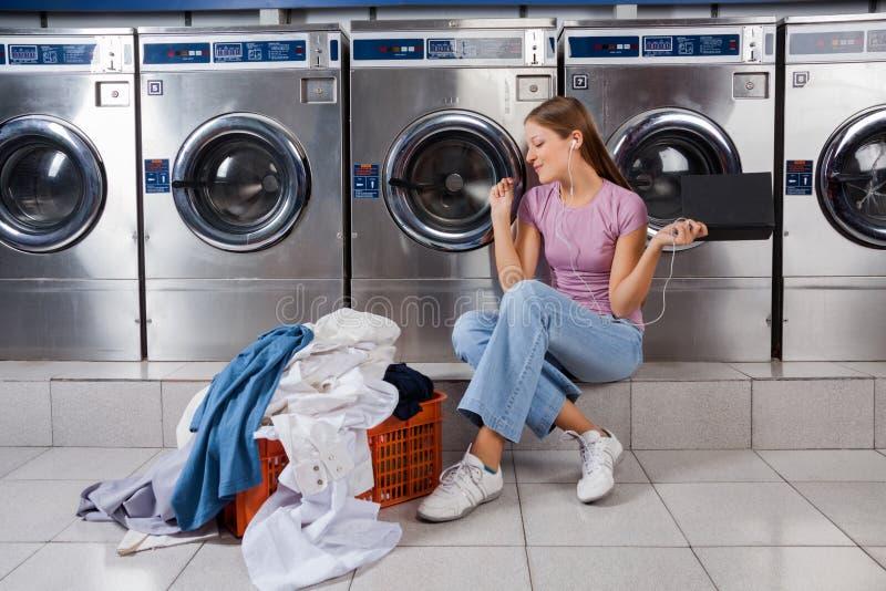 Woman Enjoying Music In Laundry stock photos