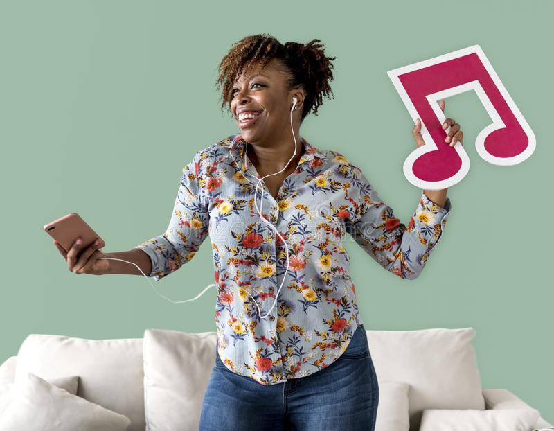 Woman enjoying music with notes cut out stock images