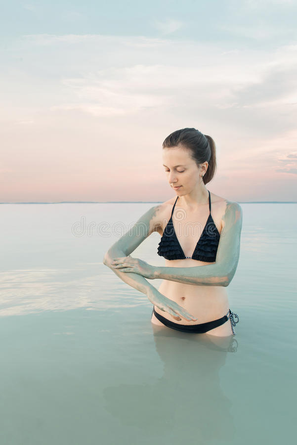 Woman enjoying the natural mud mineral source on dead sea background royalty free stock photography