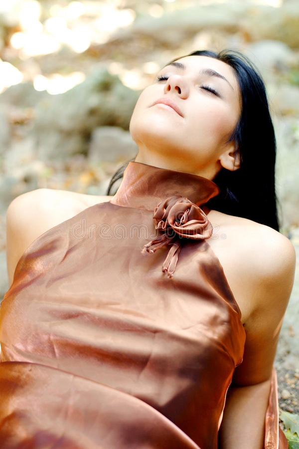 Woman enjoying nature lying in park. Beautiful young brunette girl smiling with closed eyes stock photo