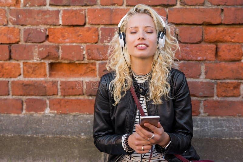 Woman enjoying peacefull music on her headphones royalty free stock images