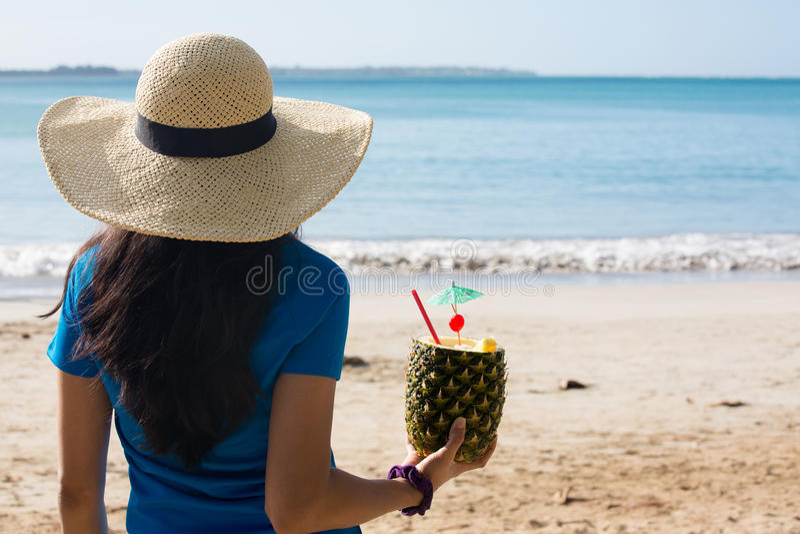 Woman enjoying pineapple drink on sunny day stock image