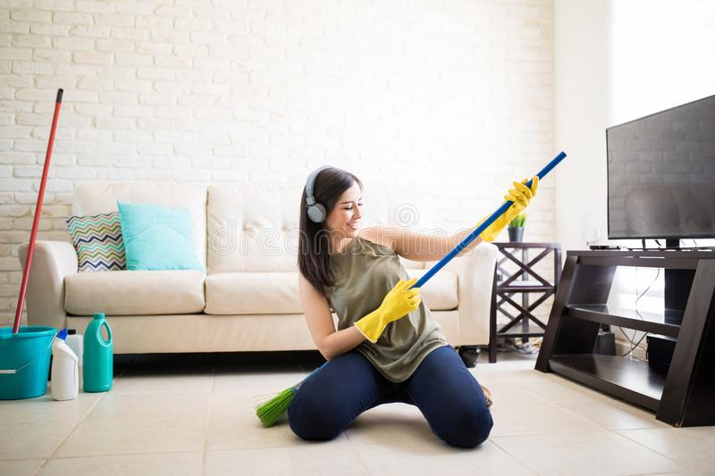 Woman enjoying playing with broom royalty free stock photography
