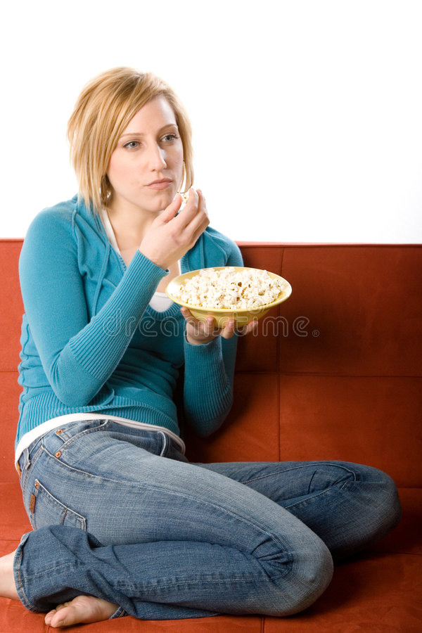 Woman enjoying popcorn. A young casually dressed woman wearing jeans and a blue pullover top, sits curled up on a red sofa, enjoying a bowl of popcorn royalty free stock image