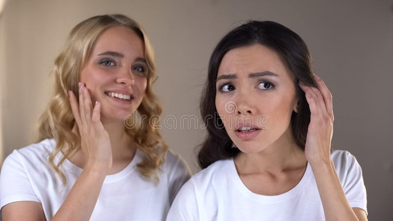 Woman enjoying reflection in mirror, her friend noticing first wrinkles, beauty. Stock photo royalty free stock photos