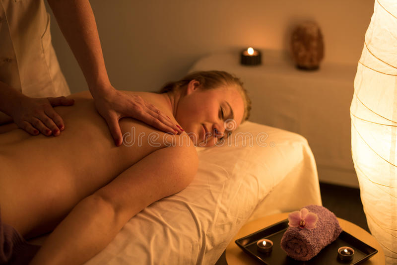 Woman enjoying relaxing back massage in cosmetic spa centre in s royalty free stock image
