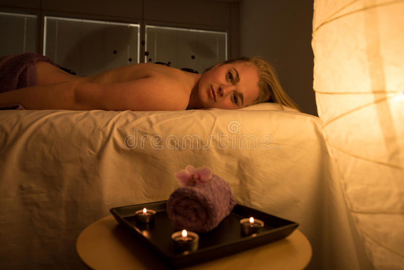 Woman enjoying relaxing back massage in cosmetic spa centre in s royalty free stock images