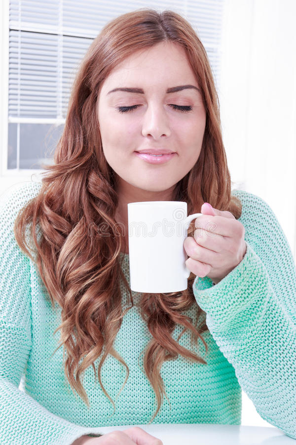 Woman enjoying the smell of coffee in the morning. With eyes closed, pensive girl smelling coffee with eyes closed daydreaming stock images