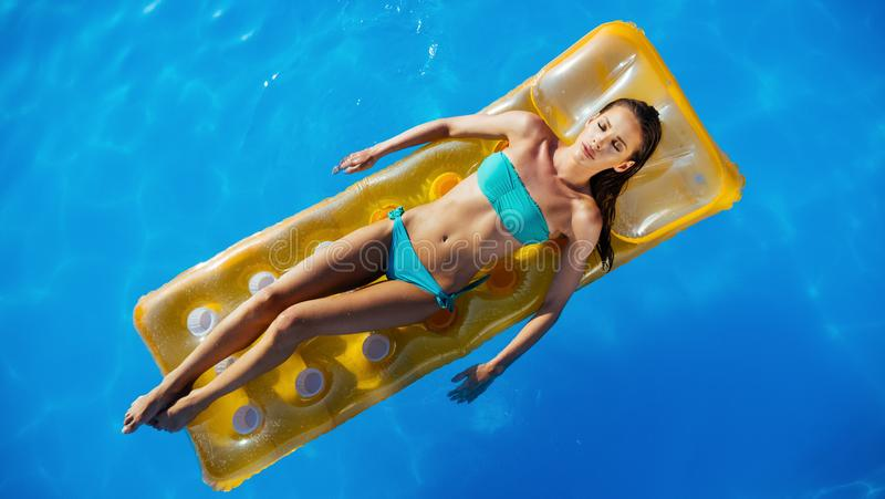 Woman enjoying summer on mattress. In swimming pool royalty free stock image