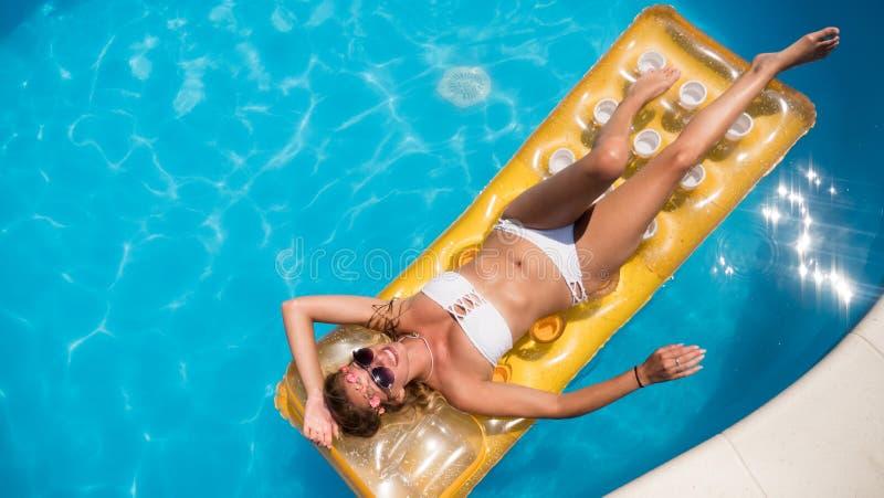 Woman enjoying summer on mattress. In swimming pool royalty free stock images