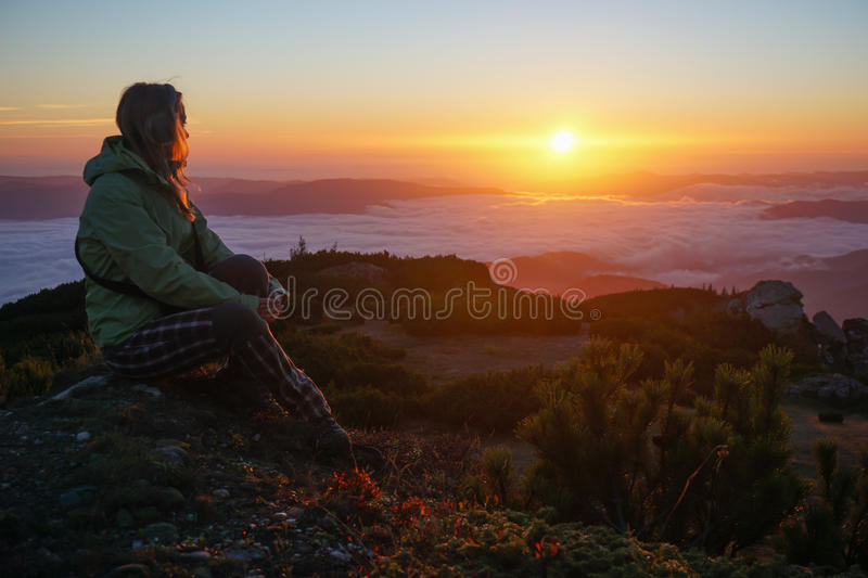 Woman enjoying the sunrise in the mountains. Of Romania stock image