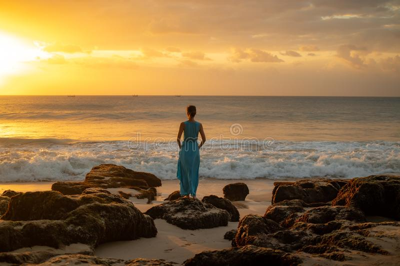 Woman enjoying sunset at the beach. View from back royalty free stock photography