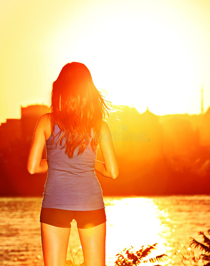 Woman enjoying sunset sunshine after running. And training outdoor. Sporty girl enjoying beautiful sunny sunshine relaxing outside after workout royalty free stock photos