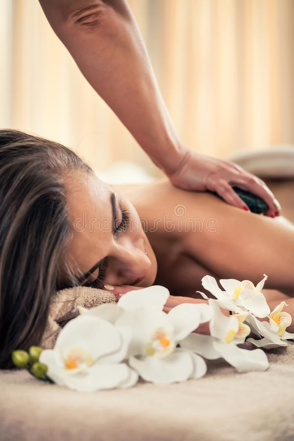 Woman enjoying the therapeutic effects of a traditional hot stone massage stock photos