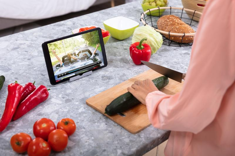 Woman Enjoying The Video While Cutting Cucumber stock photography