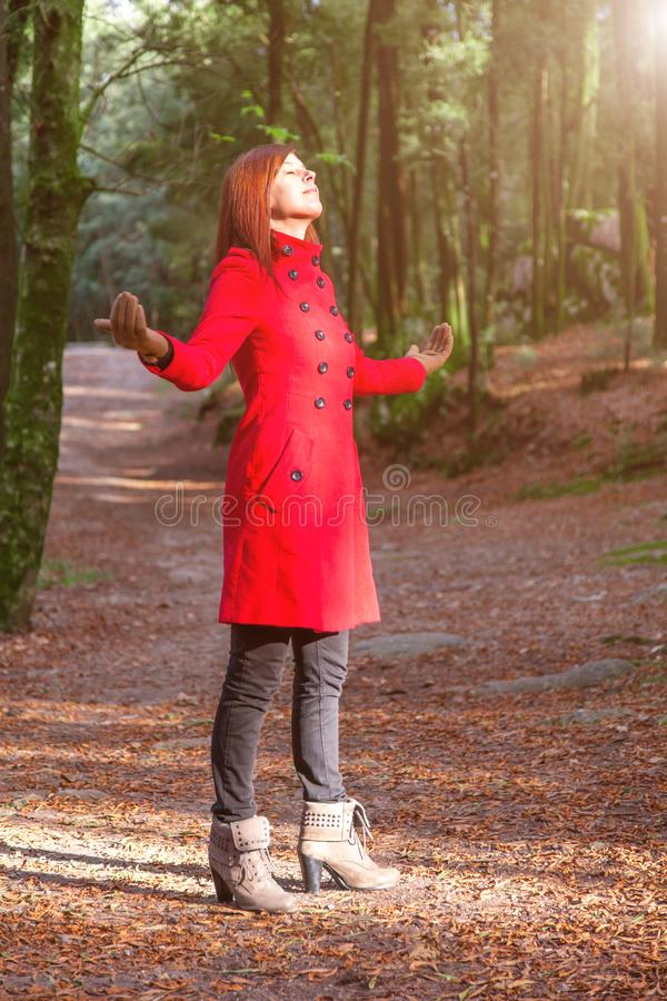 Woman enjoying the warmth of winter sunlight alone on forest park path with arms open royalty free stock photography