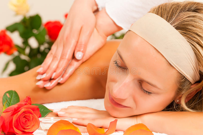 Woman enjoying wellness back massage. Woman enjoying a wellness back massage in a spa setting with roses in the background, she is very relaxed (close-up royalty free stock photography