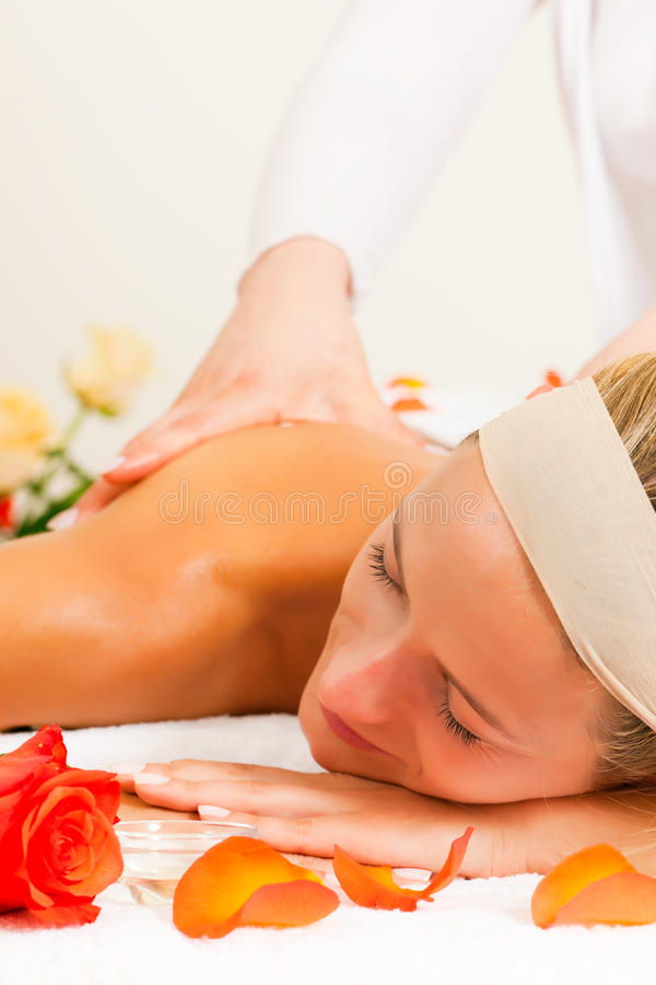 Woman enjoying wellness back massage. Woman enjoying a wellness back massage in a spa, she is very relaxed (close-up stock photography