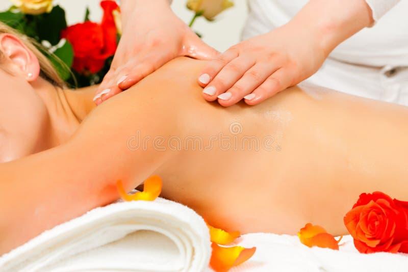 Woman enjoying wellness back massage. Woman enjoying a wellness back massage in a spa, she is very relaxed (close-up stock photos