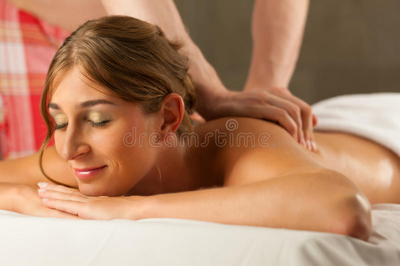 Woman enjoying wellness back massage. Woman enjoying a wellness back massage in a spa, she is very relaxed (close-up); the masseur could be her boyfriend royalty free stock image