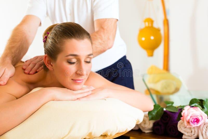 Woman enjoying wellness back massage. Woman enjoying a wellness back massage in a spa, she is very relaxed (close-up royalty free stock image