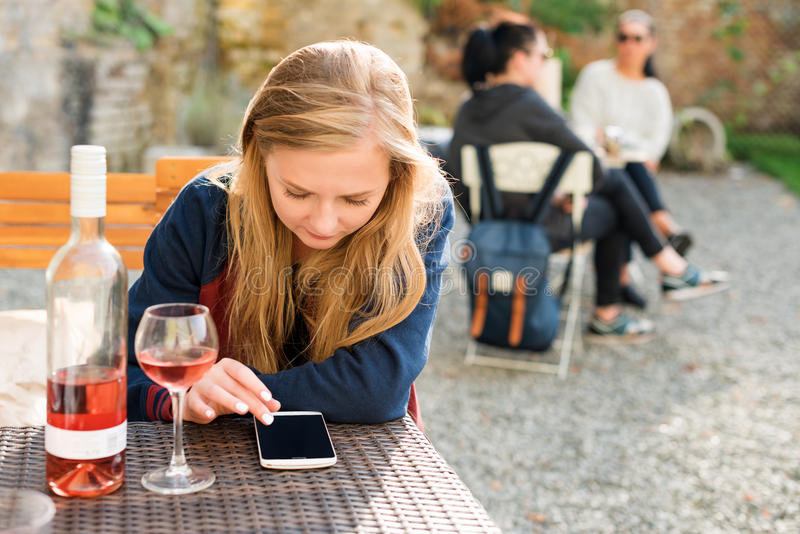 Woman enjoying wine in city street restaurant terrace. Wine tasting tourist girl sitting at the table in sidewalk cafe and using royalty free stock photo