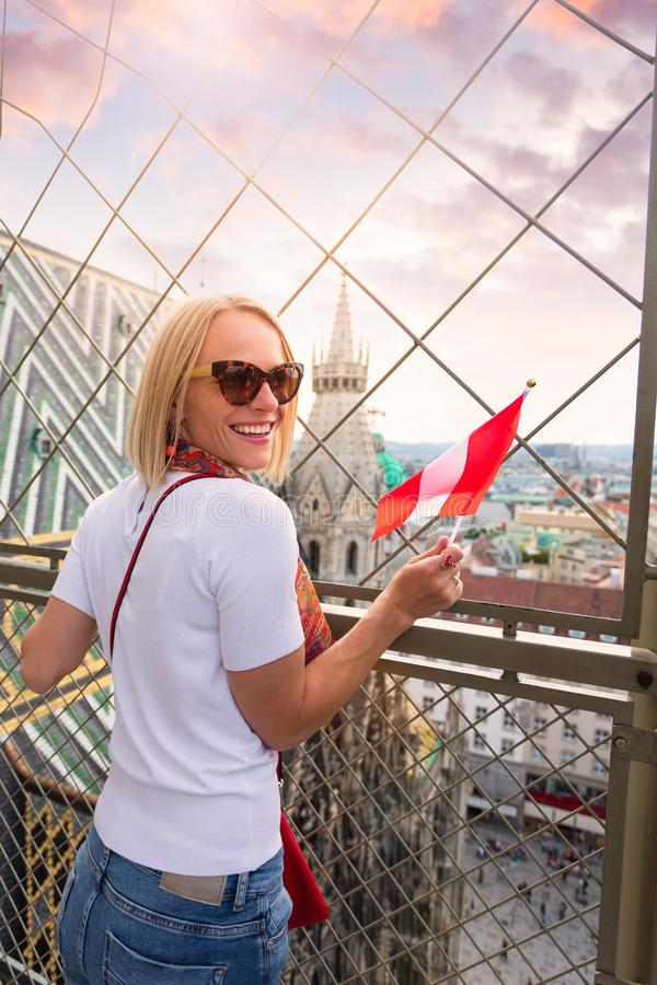 A woman admires the panorama of Vienna from the viewpoint of St. Stephen`s Cathedral and holds the flag of Austria in royalty free stock photos