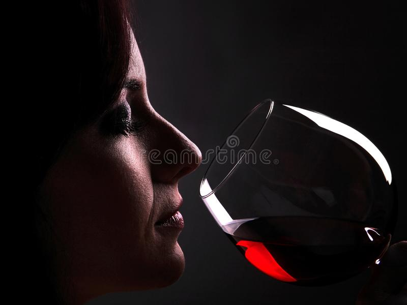 Woman enjoys the taste and the bouquet of a glass of red wine stock image