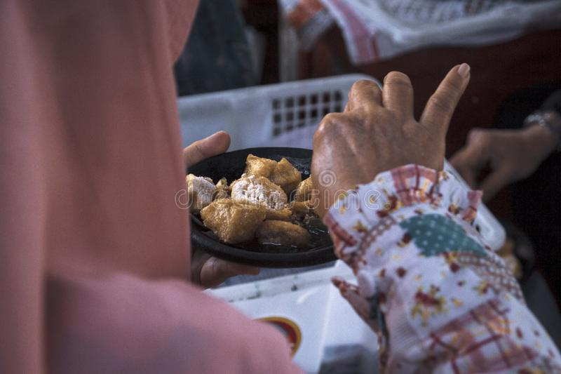 A woman enjoys traditional food fried tofu mixed crushed chilli, garlic, shallot and sauce in the market stock photography