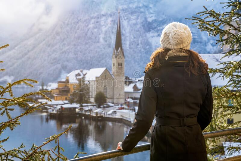 Woman enjoys the view to the beautiful village of Hallstatt in the Austrian Alps royalty free stock photo