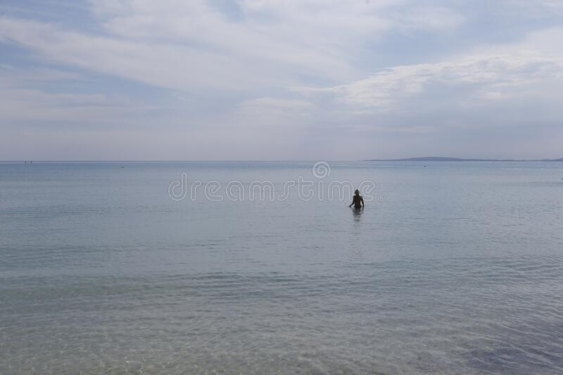 A woman enter to bath in the sea in El Arenal Beach royalty free stock image