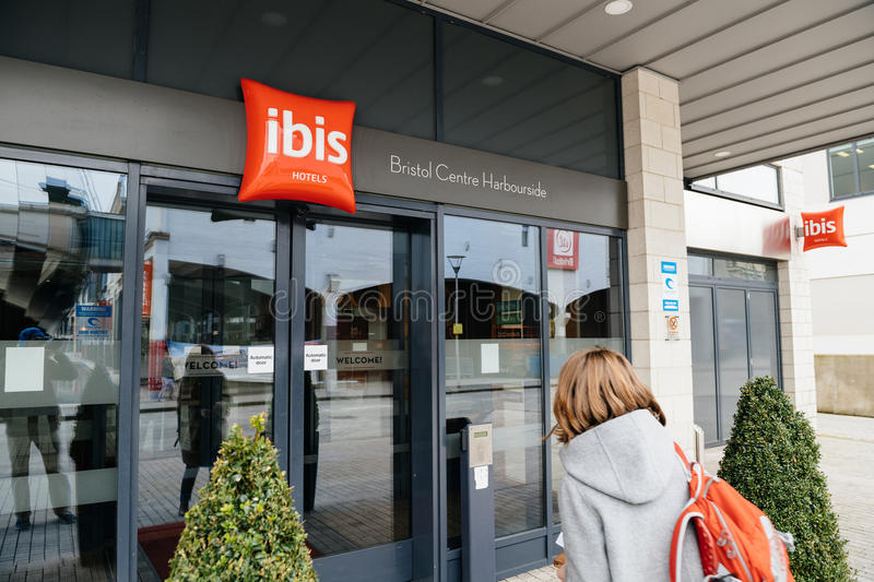 Woman entering the ibis hotel entrance welcome door with red signage royalty free stock images