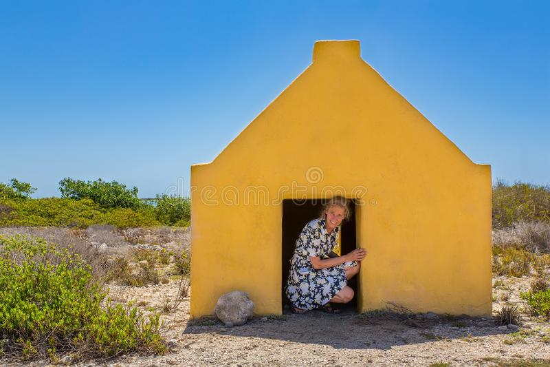Woman entering yellow slave house at coast royalty free stock photo