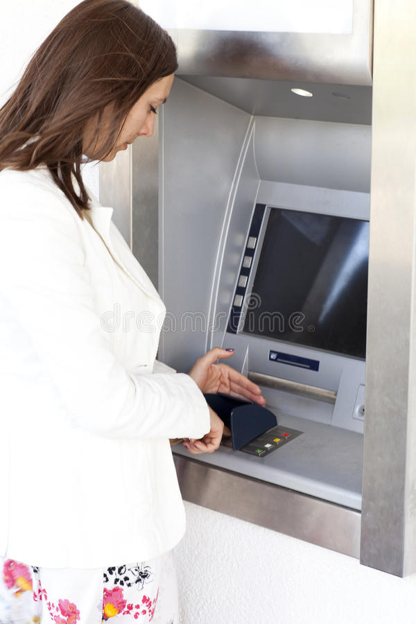 Woman enters PIN number. Attractive woman enters the PIN number at the ATM royalty free stock photos