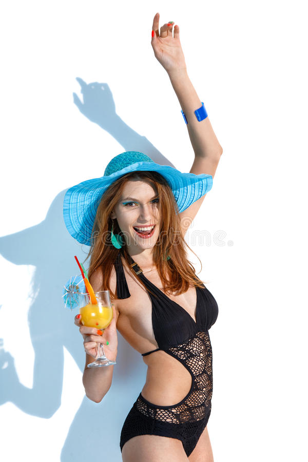 Woman entertain herself. Stock image of joyful woman in black swimwear with refreshing summer drink in her hand on white background royalty free stock photos
