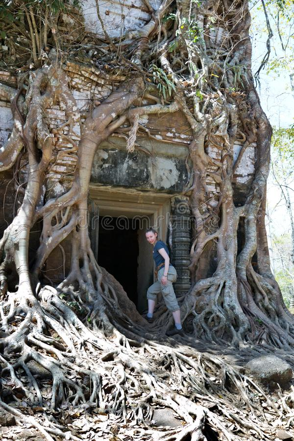 woman at an entrance to the destroyed covered with roots of trees temple Prasat Chrap in the Koh Ker temple complex, Siem Reap, C stock photo
