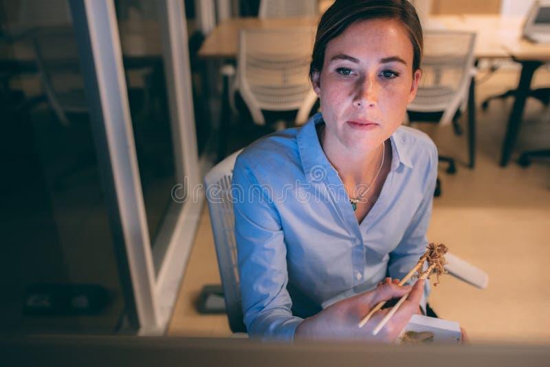 Woman entrepreneur sitting in office having dinner royalty free stock photos
